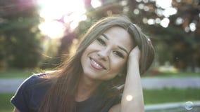Ung lycklig kvinna som ser kameran som ler, vind i hår Materiellängd i fot räknat långsam rörelse arkivfilmer