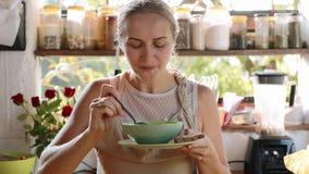 Ung lycklig kvinna som smakar precis att förbereda mat i köket stock video