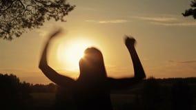 Ung lycklig kvinnabanhoppning, dans och hagyckel i skogen på solnedgången