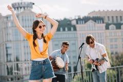 Ung lycklig kvinnadans till musik som spelas av buskers royaltyfria foton
