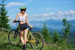 Ung lycklig kvinnaridningcykel i bergen på sommardagen arkivbild