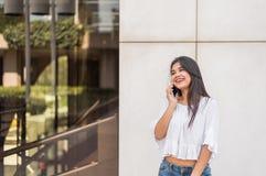 Ung lycklig kvinnatalikng och smsande meddelande med hennes mobil ph Royaltyfri Foto