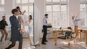 Ung lycklig kvinnlig dans för kontorsarbetare samman med multietniska kollegor på rolig företags partiultrarapid arkivfilmer