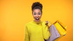 Ung lycklig kvinnlig som rymmer färgrika shoppa påsar, försäljningsöverraskning, consumerism royaltyfria foton