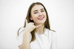 Ung lycklig le brunettkvinna med appell mig gest royaltyfri fotografi
