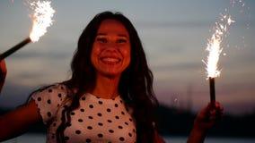 Ung lycklig le kvinna som in dansar med tomteblosset på solnedgången i ultrarapid, med fyrverkerier på solnedgången på stranden stock video