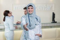 Ung lycklig le kvinnlig muslimdoktor som ger handen för handshaking Arkivbild