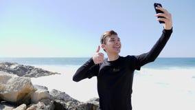 Ung lycklig le man som tar bilder av honom som skrattar och visar tummar upp på en stenig strand med att plaska för vågor lager videofilmer