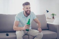 Ung lycklig le skäggig man i tillfällig kläder som sitter på sof Royaltyfri Foto