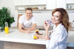Ung lycklig make i kökomsorgen för hans fru Kvinna som äter munken och dricker fruktsaft Lovestory förälskat par royaltyfria bilder