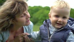 Ung lycklig mammavisningförälskelse och affektion till hennes son I parkera stock video