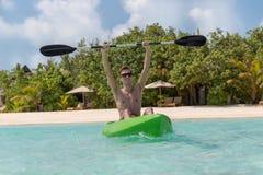 Ung lycklig man med armar lyftt kayaking på en tropisk ö i Maldiverna bl?tt klart vatten arkivfoton
