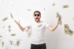Ung lycklig man med ett skägg i det vita skjortaanseendet under pengar arkivfoton