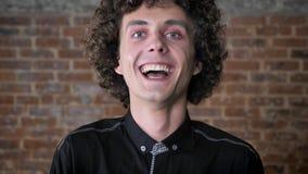 Ung lycklig man med lockigt hår som ser kameran och skrattar, bakgrund för tegelstenvägg stock video
