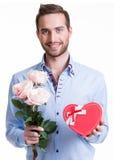 Ung lycklig man med rosa rosor och en gåva. Fotografering för Bildbyråer
