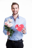 Ung lycklig man med rosa rosor och en gåva. Arkivbild