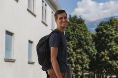 Ung lycklig man med ryggs?cken som g?r till skola efter sommarferier royaltyfri foto