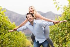 Ung lycklig man som bär den lyckliga kvinnan på hans baksida Arkivbilder