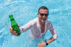 Ung lycklig man som festar i simbassäng arkivbilder