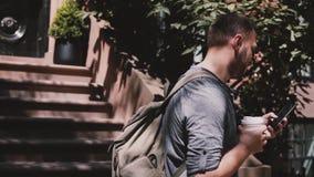 Ung lycklig man som går ner trappan av ett Brooklyn hus i New York som ler, med smartphone- och kaffeultrarapid lager videofilmer