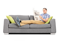Ung lycklig man som läser nyheterna på en soffa Arkivfoton