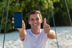 Ung lycklig man som placeras på en gunga som visar en vertikal telefonskärm Vit sand och djungel som bakgrund royaltyfri bild