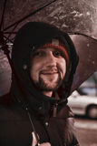 Ung lycklig man under paraplyet som ser att le för kamera Dåligt väder Arkivbilder