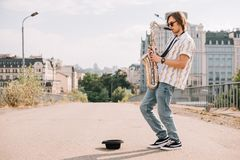 Ung lycklig manlig busker som spelar saxofonen fotografering för bildbyråer