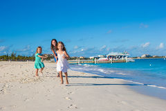 Ung lycklig moder och hennes förtjusande döttrar som har gyckel på den exotiska stranden på solig dag Arkivfoto