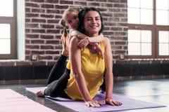 Ung lycklig moder som gör sträcka övning på mattt medan hennes le dotter som kramar henne i sportklubba arkivbild