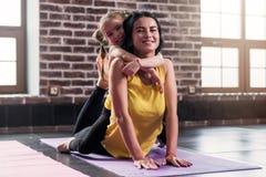 Ung lycklig moder som gör sträcka övning på mattt medan hennes le dotter som kramar henne i sportklubba fotografering för bildbyråer