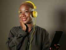 Ung lycklig och attraktiv afro amerikansk kvinna med gul hörlurar och mobiltelefonen som lyssnar till internetmusiksången som ler Arkivbilder