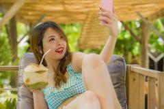 Ung lycklig och attraktiv koreansk studentflicka på den tropiska semesterortträdgården som dricker kokosnötvatten som tar selfief fotografering för bildbyråer