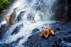 Ung lycklig och attraktiv kvinna som gör yogaövningen som poserar under den härliga tropiska vattenfallet som får vått le lycklig Arkivbilder