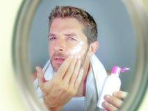 Ung lycklig och attraktiv man som applicerar fuktighetsbevarande hudkrämlotion eller anti-åldras skönhetkräm som ler säkert och m arkivbilder