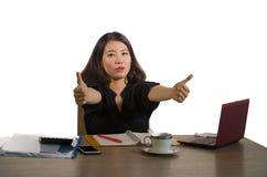 Ung lycklig och härlig asiatisk kinesisk affärskvinna som firar den upphetsade geende tummen för lyckad jobbprestation upp att ar arkivfoton