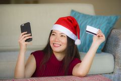 Ung lycklig och härlig asiatisk kinesisk kvinna i kreditkort för Santa Claus hattinnehav genom att använda mobiltelefonen för jul arkivfoton
