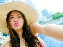 Ung lycklig och härlig asiatisk kinesisk turist- kvinna som tar selfiebilden med mobiltelefonkameran på oändlighetsbajset för lyx royaltyfri foto