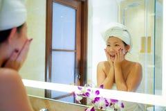 Ung lycklig och härlig asiatisk koreansk kvinna hemma eller hotellbadrum som slås in i toaletthandduken som applicerar gladlynt m fotografering för bildbyråer