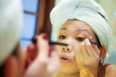 Ung lycklig och härlig asiatisk koreansk kvinna hemma eller hotellbadrum som slås in i toaletthandduken som applicerar gladlynt m arkivfoton