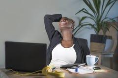 Ung lycklig och lyckad svart afro amerikansk kvinnabenägenhet på upphetsat och glat arbete för kontorsstol på skrivbordet för bär arkivfoto
