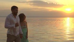 Ung lycklig parspring på stranden på solnedgången Begrepp av förälskelse arkivfilmer