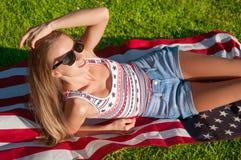 Ung lycklig patriotkvinna som rymmer den Förenta staterna flaggan Royaltyfri Foto