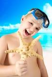 Ung lycklig pojke som har gyckel på den tropiska stranden Royaltyfria Bilder