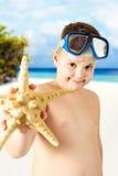Ung lycklig pojke som har gyckel på den tropiska stranden Arkivbilder