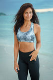 Ung lycklig stilfull sportkvinna som poserar på havskusten arkivfoto