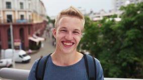Ung lycklig stilig grabb som ler på stadsgatan lager videofilmer