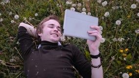 Ung lycklig student som använder minnestavlan i parkera och att ligga på gräset, i maskrosor, att le och att skratta lager videofilmer