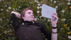 Ung lycklig student som använder minnestavlan i parkera och att ligga på gräset, i maskrosor, att le och att skratta arkivfilmer