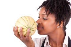 Ung lycklig svart-/afrikansk amerikankvinna som luktar en ny melo arkivfoto